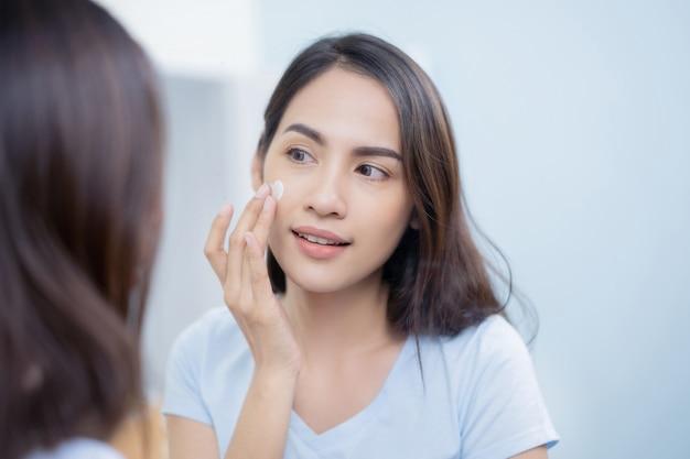 Mujeres asiáticas aplicando loción facial.