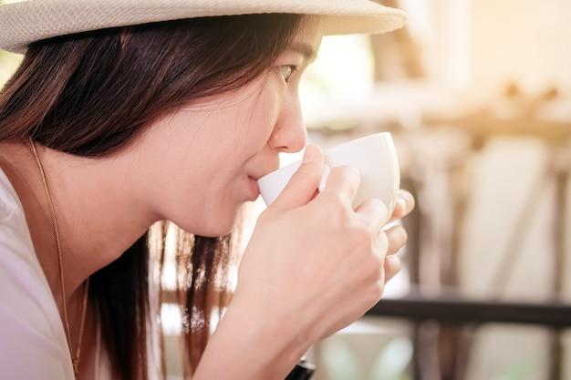 Las mujeres asiáticas beben café caliente de una taza.