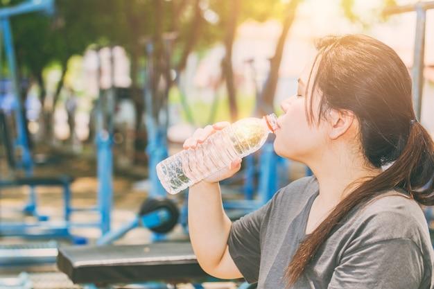 Mujeres asiáticas bebiendo agua en día caluroso ejercicio al aire libre en el parque