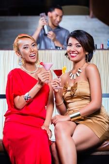 Mujeres asiáticas bebiendo cócteles en bar de lujo