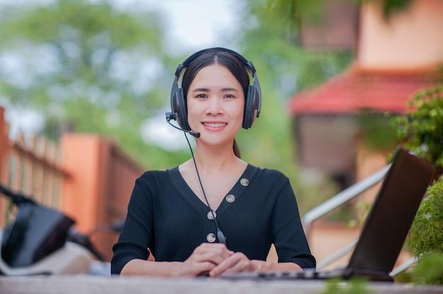 Las mujeres asiáticas de belleza son un centro de atención telefónica que ofrece un nuevo trabajo normal desde casa