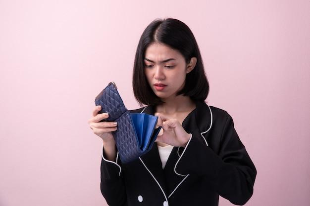 Las mujeres asiáticas de broke abren el monedero vacío aislado en fondo