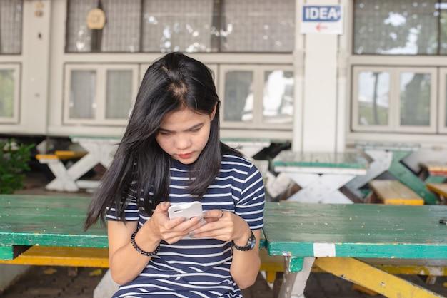 Las mujeres asiáticas broncean la piel en la cabeza y son graves con el teléfono móvil en el parque. ella se ve feliz. concepto de tarea concepto de adicto al teléfono. trabajo al aire libre. concepto de tiempo libre. copia espacio