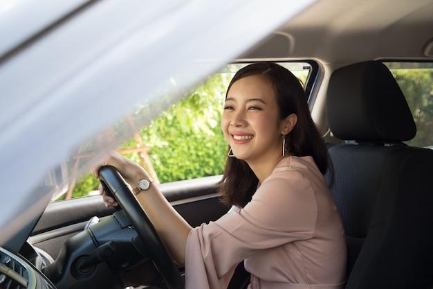 Las mujeres asiáticas conducen un automóvil y sonríen felices con alegre expresión positiva