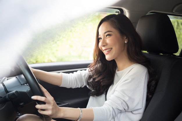 Las mujeres asiáticas conducen un automóvil y sonríen felices con una expresión positiva alegre durante el viaje en coche, la gente disfruta del transporte de risa y la mujer feliz relajada en concepto de vacaciones de viaje