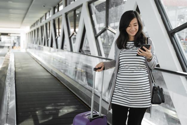 Mujeres asiáticas embarazadas ven teléfonos celulares cuando caminan por las escaleras mecánicas
