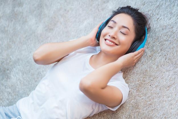 Las mujeres asiáticas escuchan música y canta en la habitación durmiendo felizmente en la alfombra.