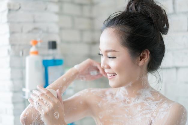 Las mujeres asiáticas se están bañando en el baño, está feliz y relajada.