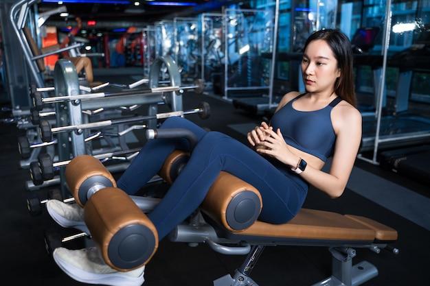 Las mujeres asiáticas están decididas a entrenar sus músculos abdominales con una pose de abdominales con un dispositivo de abdominales.
