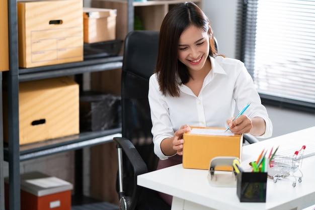 Las mujeres asiáticas están escribiendo en una caja que está en la entrega.