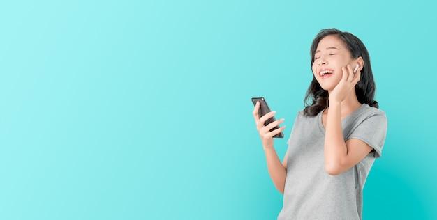 Las mujeres asiáticas de feliz sonrisa están escuchando música de auriculares blancos. y usando las manos, toque para usar varias funciones, humor feliz en azul.