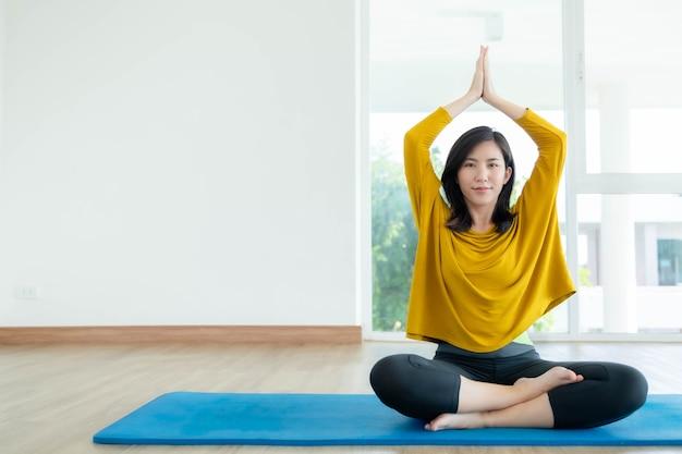 Las mujeres asiáticas hacen yoga en casa para tener un buen cuerpo.