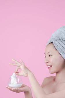 Las mujeres asiáticas hermosas están utilizando la cara de la mascarilla en la hoja en un fondo rosado.