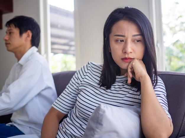 Las mujeres asiáticas hermosas piensan o se molestan por los problemas amorosos que quieren divorciarse. la esposa está estresada y triste después de una discusión con su esposo. problemas que las relaciones familiares tienen que decir adiós y acabar