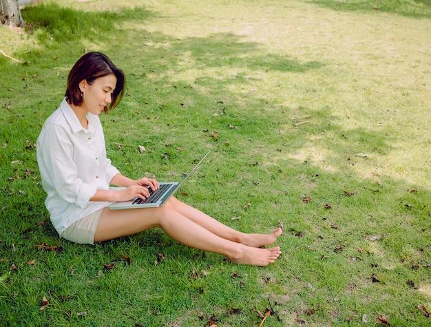 Mujeres asiáticas hermosas que llevan la camisa blanca y pantalones cortos con la computadora portátil que se sienta en hierba verde.