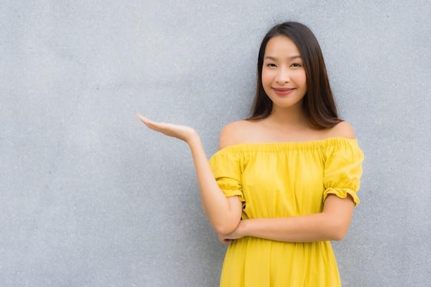 Las mujeres asiáticas hermosas del retrato sonríen felices con el fondo concreto