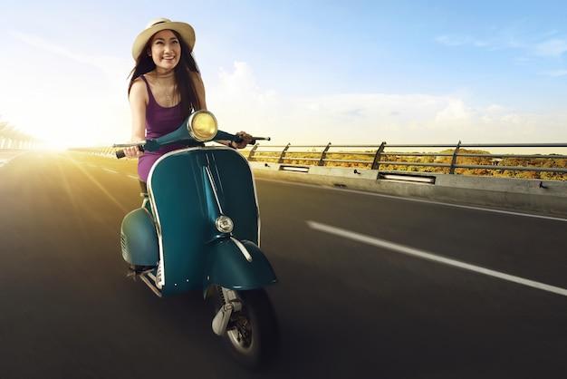 Las mujeres asiáticas jóvenes disfrutan de montar una moto y divertirse