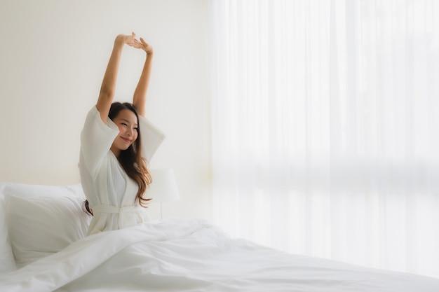 Las mujeres asiáticas jovenes hermosas del retrato sonríen felices en cama