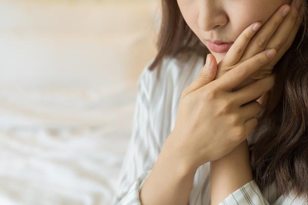 Las mujeres asiáticas jóvenes tienen dientes sensibles, dolor de muelas, caries o encías inflamadas. concepto de salud y personas enfermas.