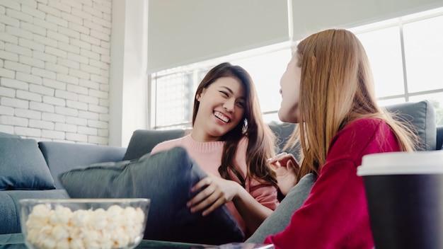 Mujeres asiáticas jugando pelea de almohadas y comiendo palomitas de maíz en la sala de estar en casa, grupo de compañero de cuarto amigo