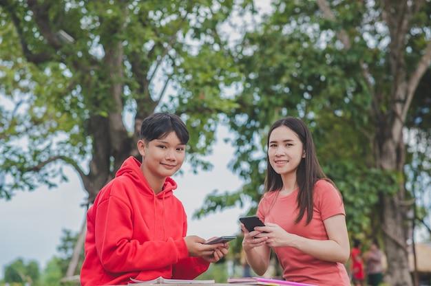 Las mujeres asiáticas con lady boy lgbt están utilizando tecnología en línea de clase de estudio de aprendizaje de búsqueda de teléfonos inteligentes móviles, concepto de educación de regreso a la escuela
