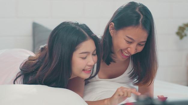 Las mujeres asiáticas lesbianas lgbtq se juntan usando la tableta en casa.