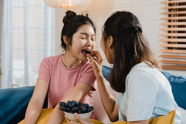 Las mujeres asiáticas lesbianas lgbtq pareja comen alimentos saludables en casa