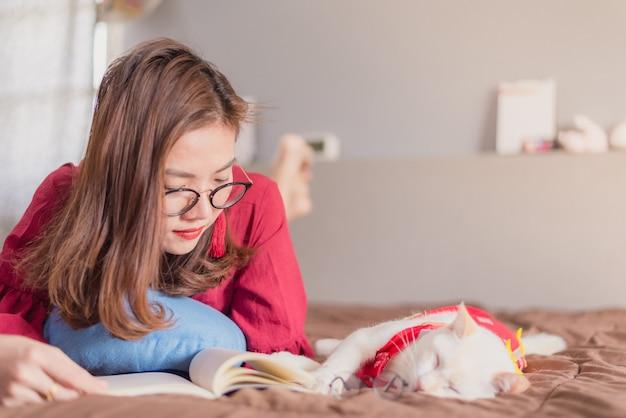 Mujeres asiáticas leyendo en la cama con un gato en casa
