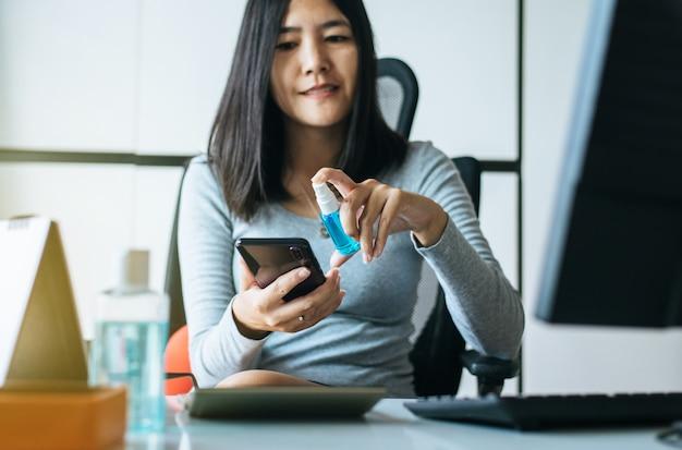 Las mujeres asiáticas mano usando rociar alcohol al teléfono inteligente