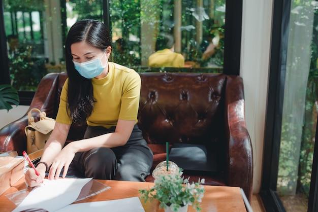 Mujeres asiáticas con máscaras médicas sentada y trabajando en vacaciones, trabaja en línea. concepto: las mujeres asiáticas son independientes.