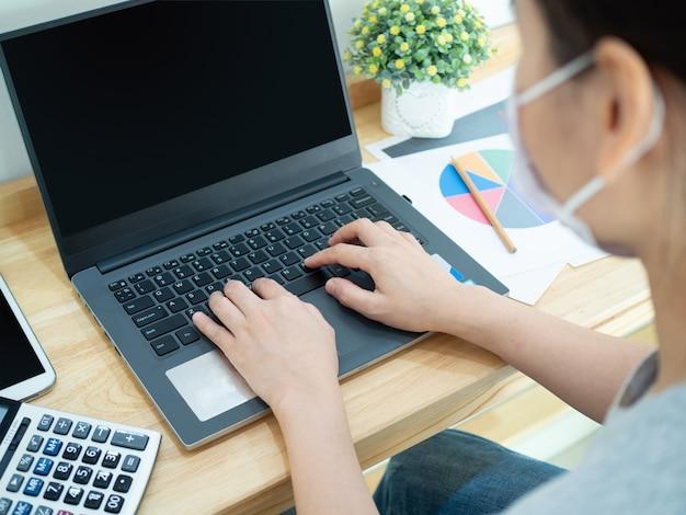 Mujeres asiáticas con máscaras que trabajan en casa y conferencias en equipo usando una computadora portátil