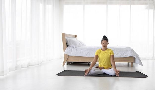 Las mujeres asiáticas meditan mientras practican yoga
