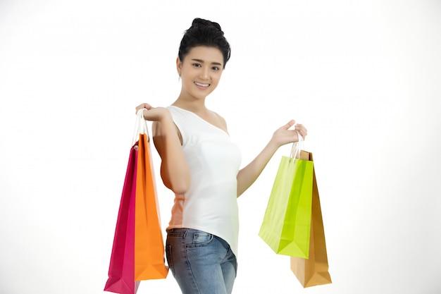 Las mujeres asiáticas y la niña hermosa están sosteniendo bolsas de compras y sonriendo.
