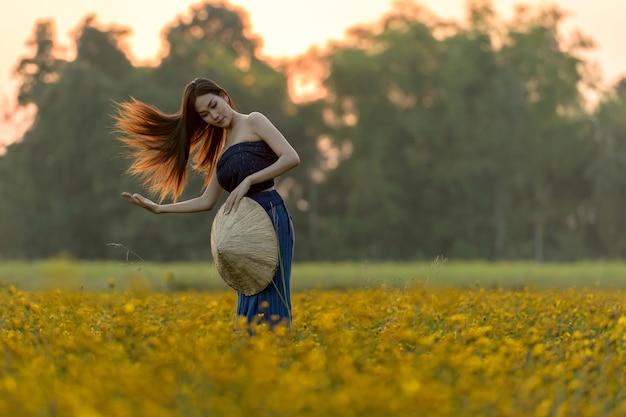 Mujeres asiáticas de pie en un hermoso campo de flores amarillas.