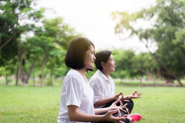 Mujeres asiáticas practicando yoga en el parque por la mañana, feliz y sonriente, pensamiento positivo, concepto de estilo de vida saludable