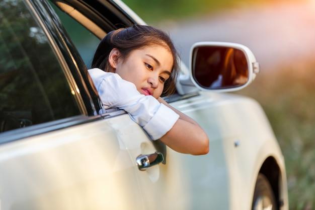 Mujeres asiáticas del primer de un coche preocupado que mira el lado a través de la ventana en un día triste