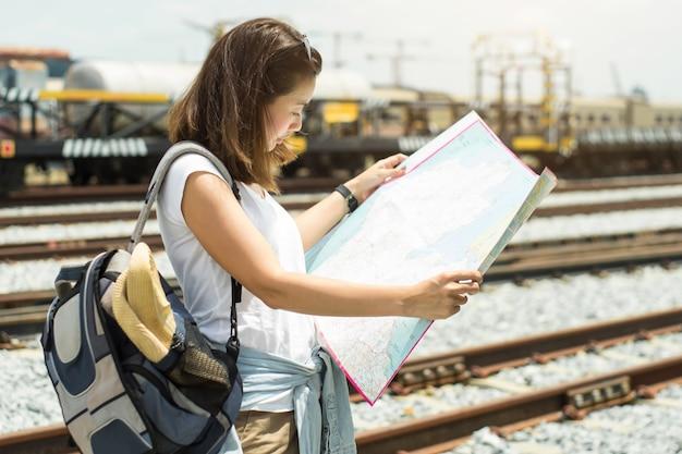 Mujeres asiáticas que buscan un mapa para viajar en tren.