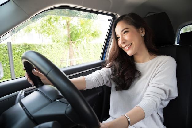 Mujeres asiáticas que conducen un automóvil y sonríen alegremente con una expresión positiva de alegría durante el viaje en automóvil