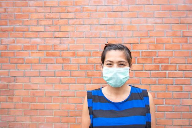 Mujeres asiáticas que llevan una pared de ladrillo del fondo de la máscara.
