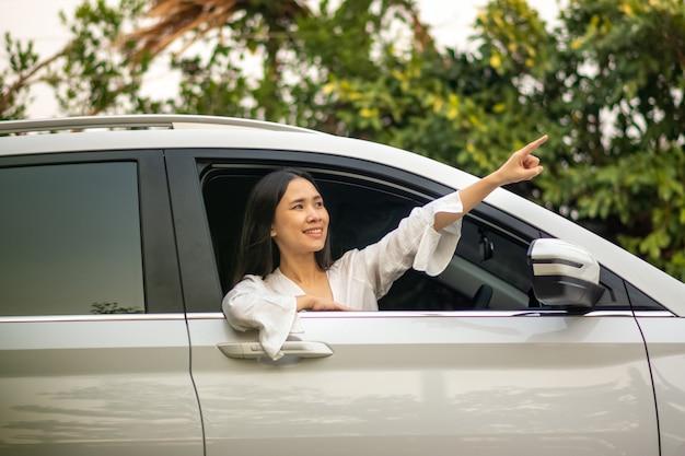 Mujeres asiáticas que se sientan en concepto de automóvil viajes de seguros de finanzas comerciales
