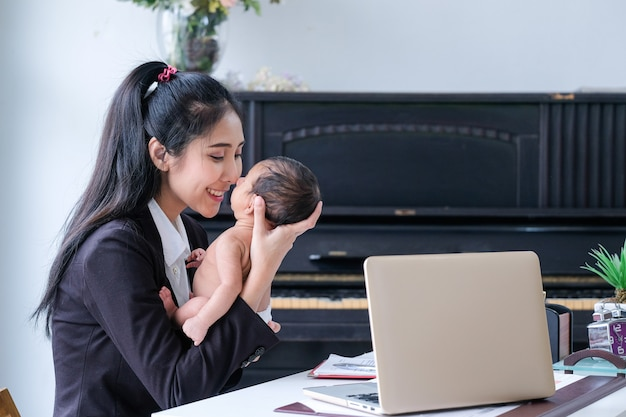 Mujeres asiáticas que trabajan en negocios y crían niños en casa