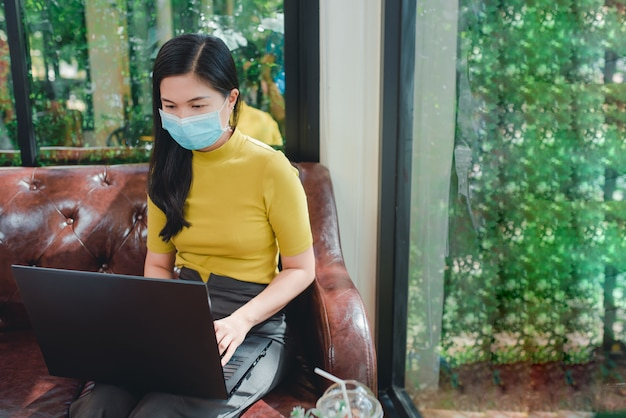 Mujeres asiáticas que trabajan en vacaciones usando una máscara de médico mientras trabajaba durante una infección virus corona o covid 19