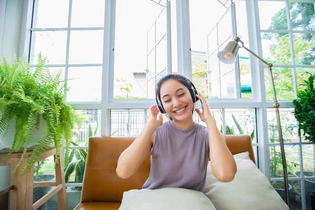 Mujeres asiáticas que usan auriculares y usan una computadora portátil y una tableta digital para escuchar música y cantar en un día relajante en casa