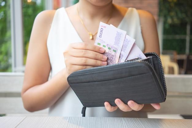 Las mujeres asiáticas recogen los billetes de banco tailandeses de la bolsa para pagar la comida o pagar los servicios.