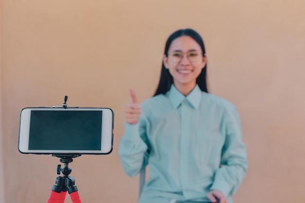 Las mujeres asiáticas son la tecnología en línea de la clase de capacitación en video blogger en línea