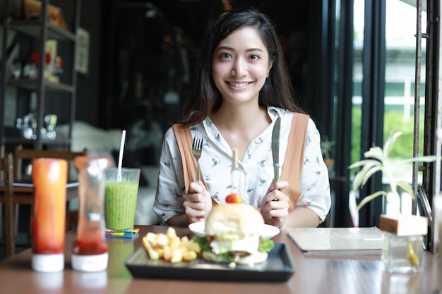 Las mujeres asiáticas sonrientes y felices y disfrutaron comiendo hamburguesas en el café y el restaurante en el momento de relajarse