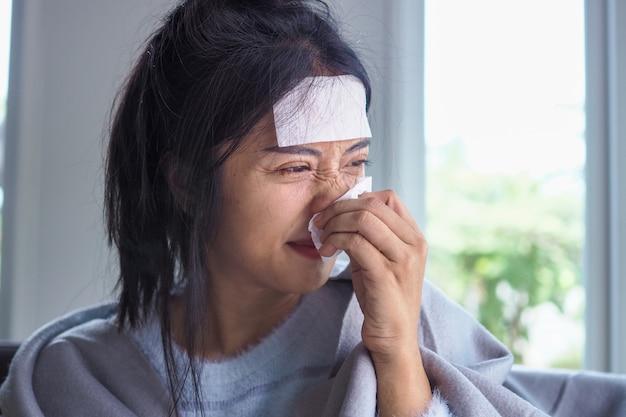 Las mujeres asiáticas tienen fiebre alta y secreción nasal. gente enferma