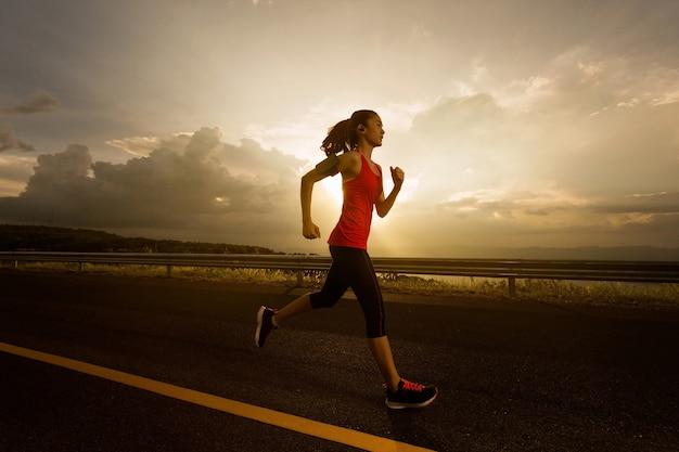 Las mujeres asiáticas trotaban por la mañana y escuchaban música mientras corrían
