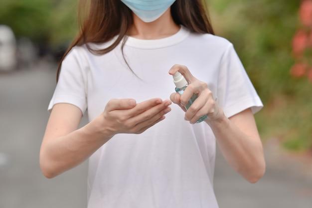 Las mujeres asiáticas usan alcohol para limpiar las manos para proteger el coronavirus covid19
