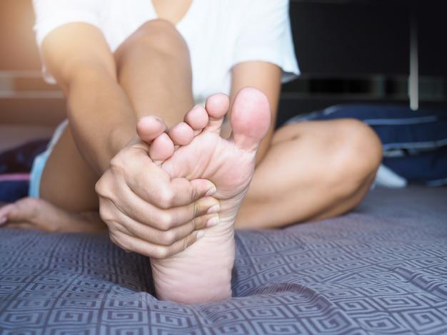 Las mujeres asiáticas usan las manos para masajear las plantas de los pies y el dolor en el talón, lesión del dolor en el pie.